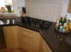 Gezellige keuken met natuurstenen werkblad en eiken fronten.